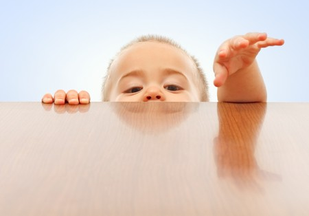 Curious little boy looking up and raising hands onto table surface