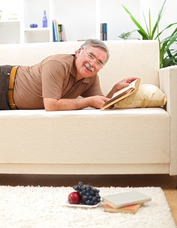 Happy senior man relaxing and reading books on sofa photo