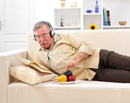 listen music: Senior man laying on sofa, reading and listening to music while eating fruits Stock Photo