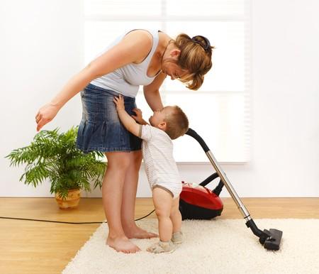 Mutter Reinigen des Bodens, während Sie Baby weint und will abgeholt werden Standard-Bild