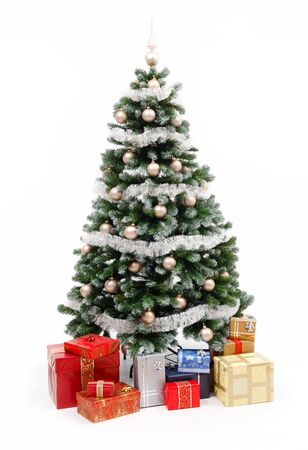 Artificial christmas tree isolated on white, decorated with golden ornaments and silver garland, a lot of presents under the tree Stock Photo