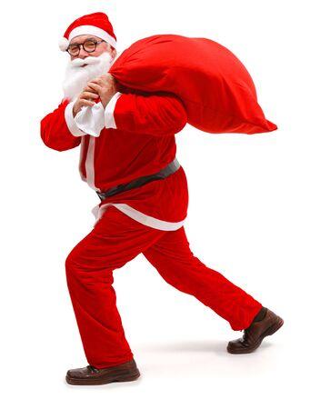 Senior man wearing Santa Claus uniform, walking with full bag photo