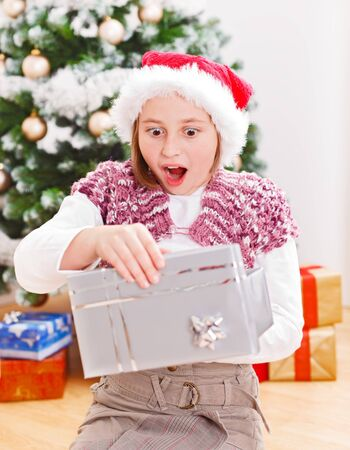 Girl opening Christmas gift box with very surprised facial expression photo