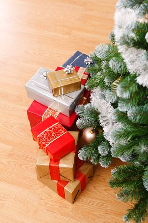 Lots of presents under the decorated artificial Christmas tree photo