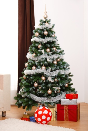 Decorated artificial Christmas tree in room,  presents under