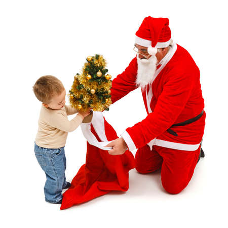 knelt: Little boy putting a small, decorated Christmas tree in Santa Clauss bag