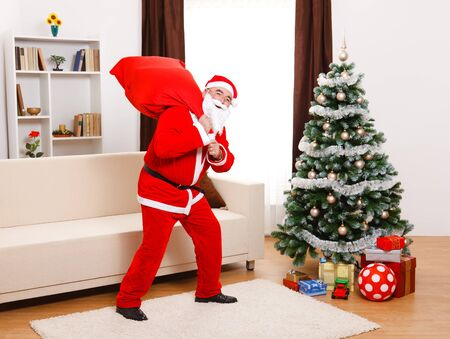 Senior man, wearing Santa Claus uniform, in front of Christmas Tree, walking away with full bag on the back photo