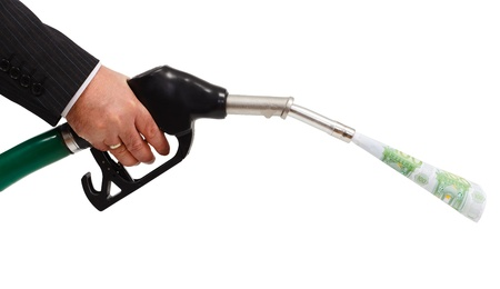 Hand holding gas nozzle, money pouring from pipe photo