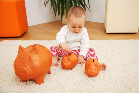 Little baby boy sitting and inserting coin into piggy bank; metaphoric view of the early savings, insurance or investments