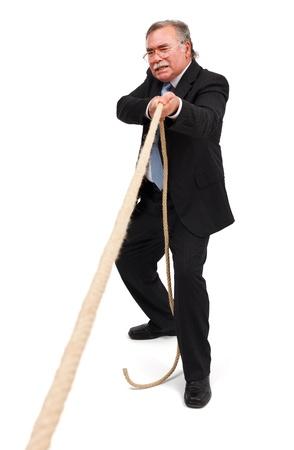 tug o war: Juego de tira y afloja; hombre de negocios Senior tirando duro, solo una cuerda
