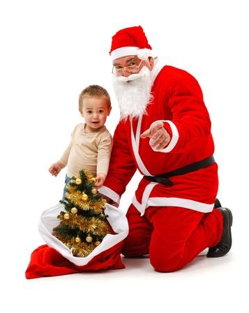 Senior man wearing Santa Claus uniform; bringing attention of a baby boy photo