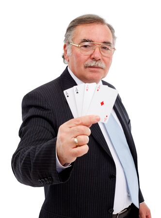 Senior man holding playing cards, showing all trumps, the four aces Stock Photo - 9119631