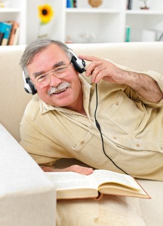 Happy senior man laying on sofa, listening to music while reading photo