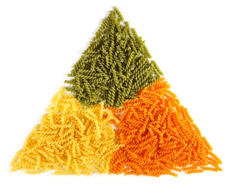 colorant: Bunch of naturally colored twisted pasta, arranged in triangle shape Stock Photo