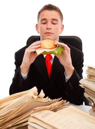 Man taking a break during paperworks, eating a sandwich photo