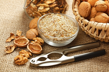 Whole walnuts, nut kernel and ground nut with nutcracker Stockfoto