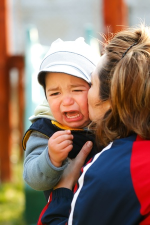 Mother embracing and kissing her little crying boy photo