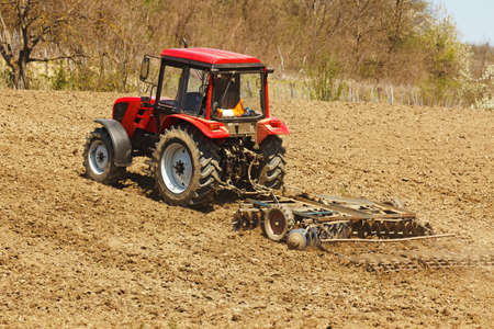 Red tractor on hill with disk harrow and rake photo
