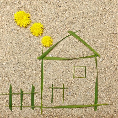 metaphoric: House and smoke illustration in sand made of grass and flowers Stock Photo