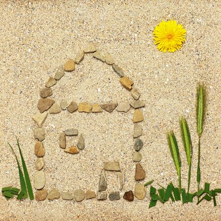 stones with flower: House illustration in sand made of pebbles, grass and flowers Stock Photo