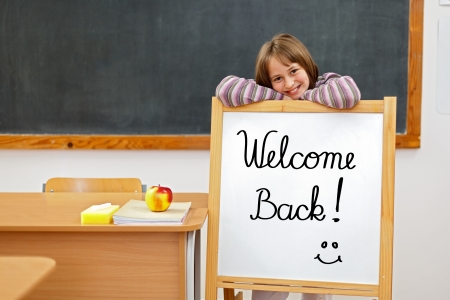 School girl in classroom, behind a board with Welcome Back script Stock Photo