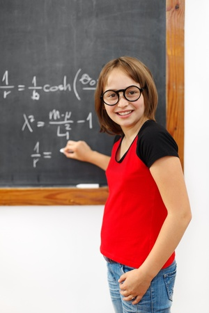 Wise school girl writing the solution of the complicated equation on chalkboard photo