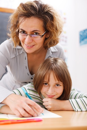 Teacher helping a school girl to write by holding her hand Stock Photo - 9993532