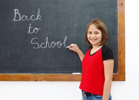 Elementary school girl writing Back to School on chalkboard photo