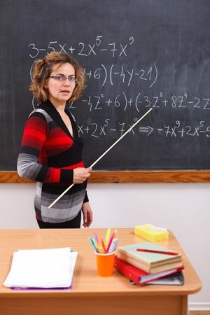 Serious math teacher explaining polynomials written on black chalkboard photo