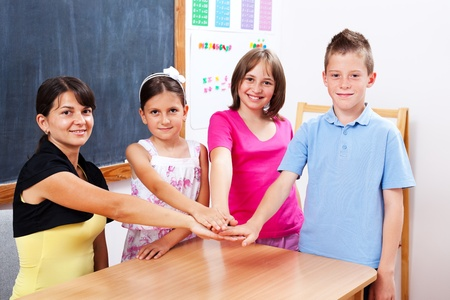 Group of united students and teacher, putting their hands together Stock Photo - 10030625