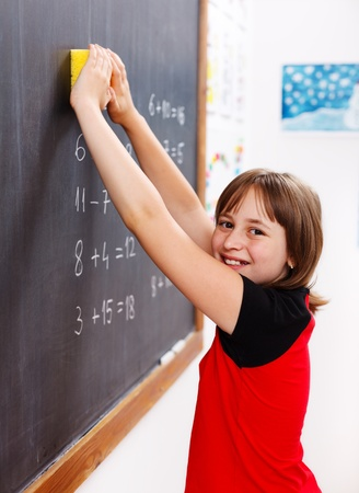 Happy elementary schoolgirl erasing chalkboard