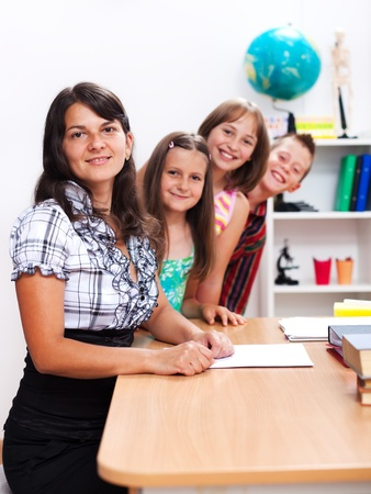 Cheerful teacher in front, several students in back Stock Photo - 10030582