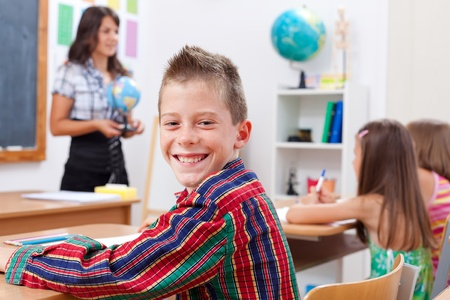 Cheerful young boy smiling in classroom while the teacher explains photo