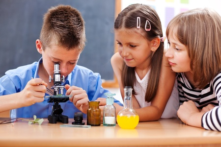 science class: Eminent elementary school boy looking into microscope while girls are watching Stock Photo