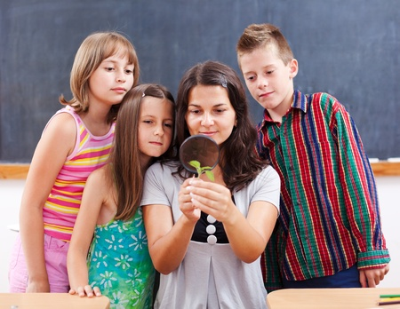Teacher and students keen look at a plant through magnifier photo