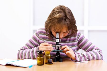 Schoolgirl looking into microscope in biology class Stock Photo - 9993689