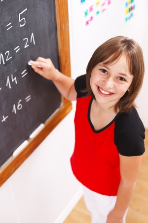 maths: Schoolgirl looking up while solving math equations at chalkboard. Shallow depth of field! Stock Photo