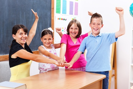 Happy winner group of united students and teacher in school, raising and holding hands together