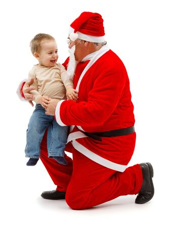 Senior man in Santa Claus uniform, holding on knee a happy little boy photo