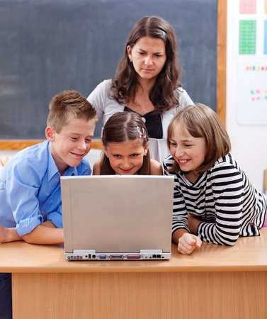 class room: Kids surfing on the internet, watching unsafe content. Teacher stands behind and worries about Stock Photo