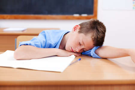 Tired boy sleeping on table in classroom photo