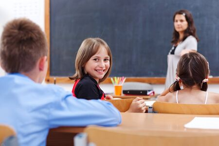 Cheerful school girl looking back in class room while the teacher explains photo
