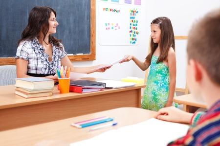 Schoolgirl standing in front of teacher, giving or receiving test paper