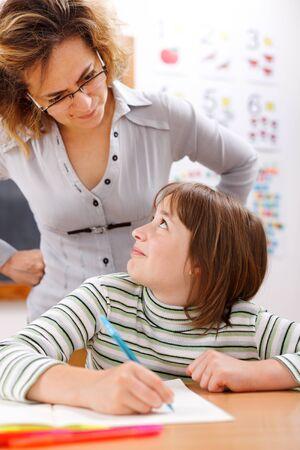 scholar: Severe teacher standing behind and looking at schoolgirl