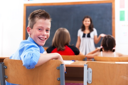 Cheerful school boy looking back in class room while the teacher explains photo