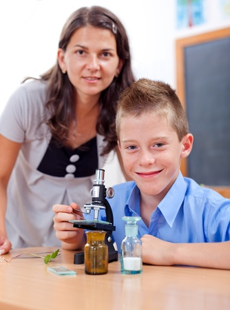 Wise boy with microscope and the biology teacher