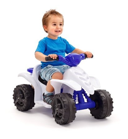Little boy sitting on plastic toy car Stock Photo
