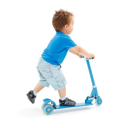 Little boy going fast with toy scooter (partial motion blur on leg)