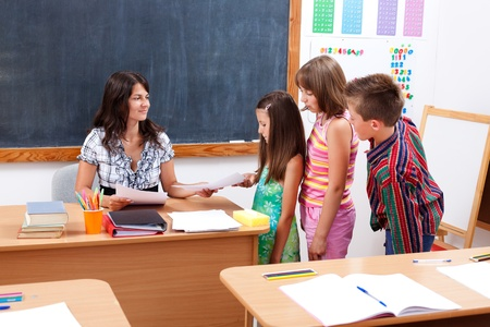 teacher in class: Children standing in row in front of teacher who gives or receives test paper