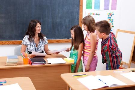 profesor alumno: Ni�os en fila delante del maestro que da o recibe el documento de prueba